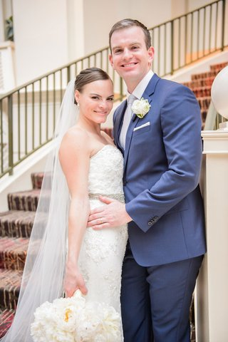 bride-in-strapless-beaded-wedding-dress-with-hair-pulled-back-and-veil-groom-in-navy-blue-suit