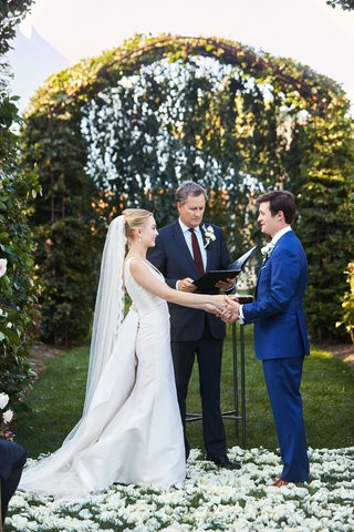 wedding-ceremony-outdoor-white-flower-petal-aisle-greenery-arch-bride-in-updo-veil-groom-blue-suit