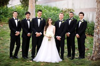 bride-in-sabrina-dahan-a-line-wedding-dress-with-groomsmen-in-black-suits-and-bow-ties