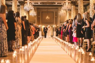 wedding-ceremony-white-aisle-runner-candles-in-glass-vases-on-sides-bride-and-father-of-bride-guests