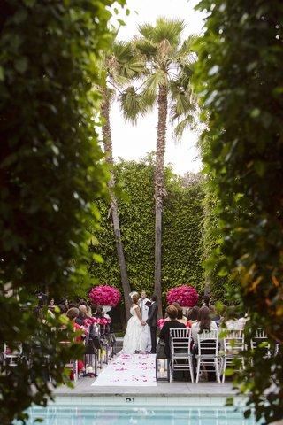 bride-and-groom-in-between-palm-trees-at-hotel-pool-wedding