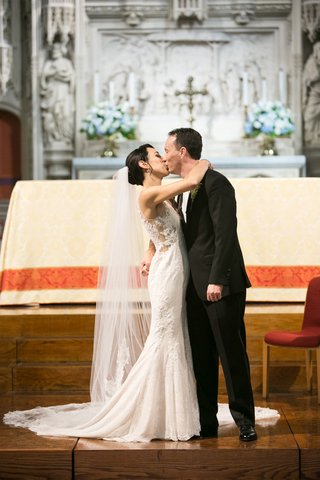 bride-in-rivini-wedding-dress-and-cathedral-veil-kisses-groom-during-church-ceremony