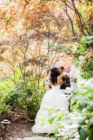 a-bride-shows-off-the-back-of-her-white-gown-while-embracing-her-groom-in-a-garden