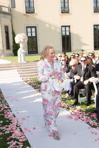 grandma-walking-down-white-aisle-runner-at-oheka-castle-in-flower-print-dress-with-matching-jacket