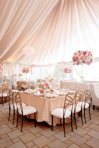 wedding-reception-tent-blush-pink-gold-chairs-white-pink-flowers-square-table-settee-tufted-sofas