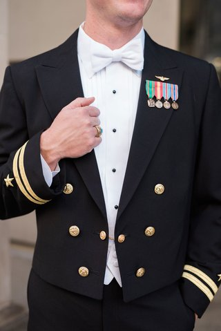 groom-in-navy-uniform-with-bow-tie-and-decorations-on-lapel