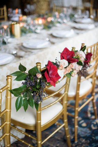 wedding-reception-head-table-bride-and-groom-chairs-decorated-with-green-leaves-red-flowers