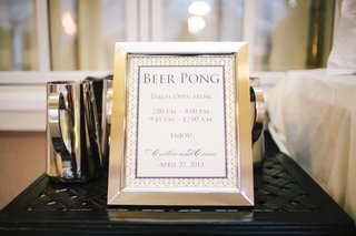 silver-framed-sign-of-beer-pong-table-hours-at-wedding