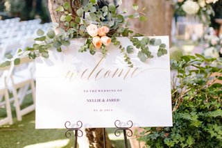 wedding-ceremony-welcome-sign-gold-calligraphy-eucalyptus-peach-rose-flowers