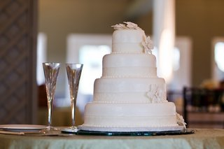 white-wedding-cake-with-crystal-champagne-flutes