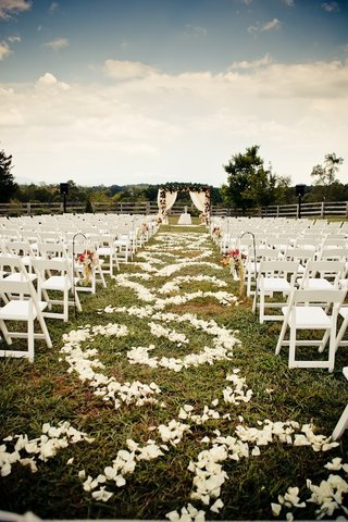 white-ceremony-chairs-and-petal-covered-aisle