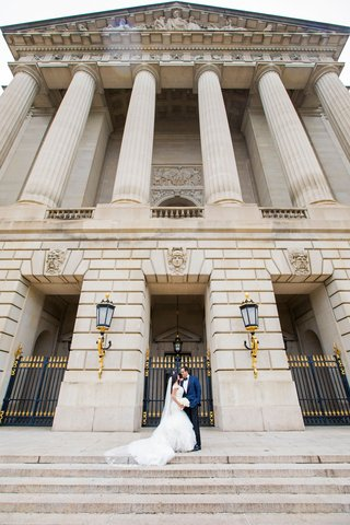andrew-w-mellon-auditorium-wedding-venue-couple-in-front-of-space-on-steps-in-between-gold-sconces