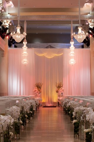 crystal-chandeliers-above-indoor-ceremony-with-drapery