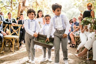 boy-ring-bearers-in-grey-pants-and-blue-suspenders-and-bow-ties-tossing-olive-sprig-leaves-on-aisle