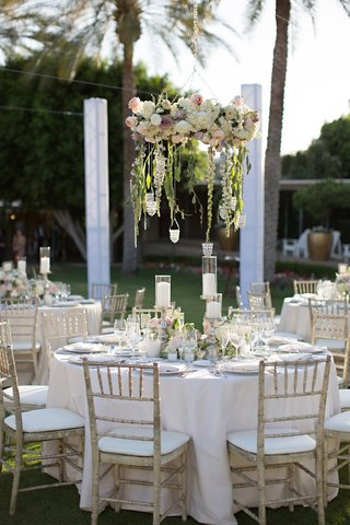 garden-wedding-reception-with-floral-chandeliers-tables-in-white-tablecloths-and-weathered-chairs