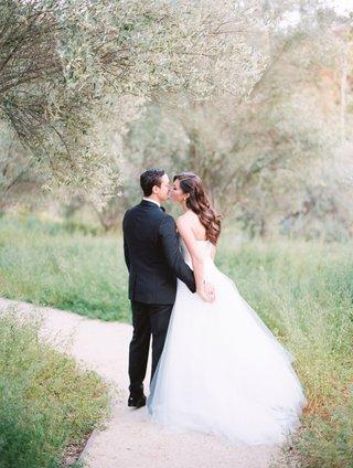 back-of-bride-and-groom-sharing-kiss-wedding-portrait-a-line-tulle-skirt-wedding-dress-tuxedo