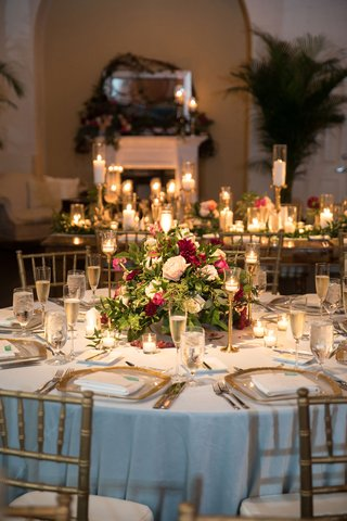 wedding-reception-with-low-centerpieces-greenery-and-burgundy-flowers-light-blue-linens-gold-chairs