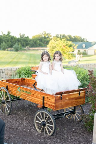 two-flower-girls-in-white-dresses-inside-wood-wagon-at-salamander-resort-spa-in-virginia