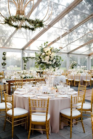 wedding-reception-clear-tent-greenery-gold-lantern-green-white-centerpiece-gold-chairs-round-table