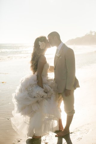 tone-it-up-katrina-hodgson-wedding-dress-monique-lhuillier-flower-in-hair-tan-grooms-suit-on-beach
