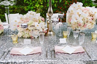 rooftop-garden-wedding-reception-table-with-sequin-tablecloth-pink-napkins-wine-glasses-with-gold