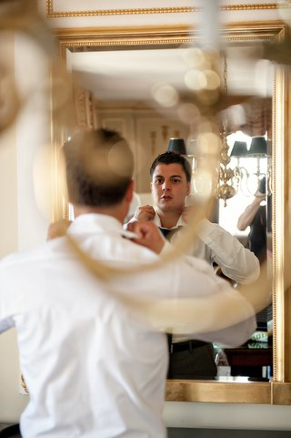 groom-looks-in-mirror-to-adjust-shirt-collar-and-tie