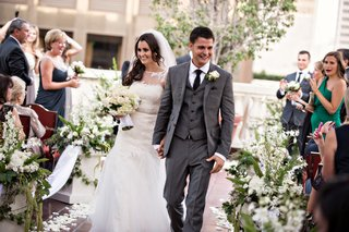 newlyweds-walk-down-aisle-lined-with-white-flowers-and-greenery