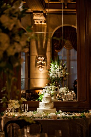 three-tiered-white-cake-on-table-covered-with-flowers