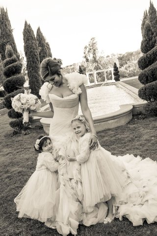 black-and-white-photo-of-bride-in-ruffle-dress-with-flower-girls-hugging-skirt-grand-del-mar