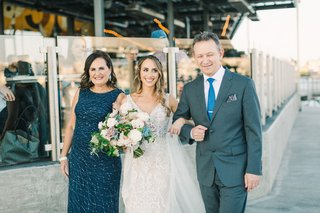 bride-in-lace-gown-walking-arm-in-arm-with-her-parents-mother-of-the-bride-in-teal-father-in-slate