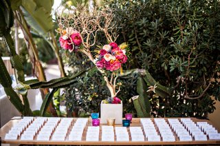 centerpiece-of-gold-branches-and-flowers-on-escort-card-table-at-wedding