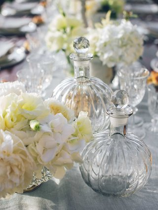 glass-bowls-with-glass-stoppers-interspersed-among-flower-arrangements