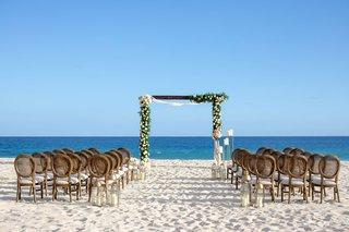 wedding-ceremony-on-sand-beach-modern-arch-greenery-pink-flower-gold-lantern-cane-round-chair-back