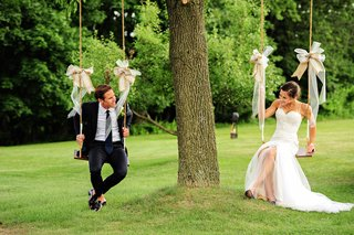 bride-in-a-berta-bridal-gown-and-groom-in-a-navy-blue-ralph-lauren-tuxedo-on-swings-with-ribbons