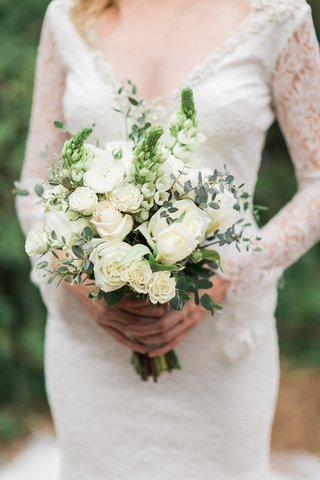 bride-in-a-long-sleeve-pronovias-lace-dress-holds-bouquet-of-white-roses-flowers-and-greenery