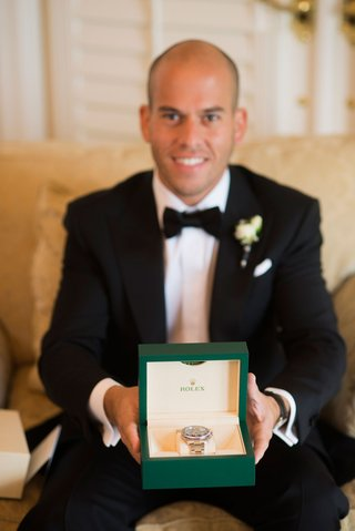groom-in-tuxedo-holding-rolex-watch-in-green-box-platinum