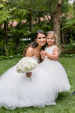 bride-in-strapless-monique-lhuillier-wedding-dress-with-peony-bouquet-and-flower-girl-dress