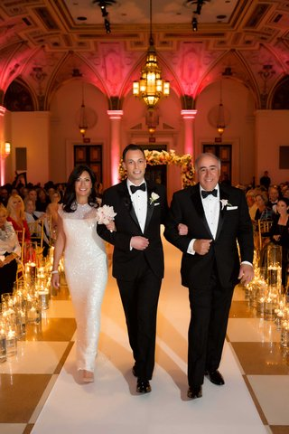 groom-in-tuxedo-walking-with-father-and-mother-of-groom-in-sparkly-sequin-white-long-dress