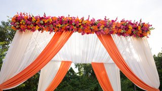 outdoor-indian-wedding-ceremony-with-a-white-and-orange-canopy-orange-pink-and-yellow-flowers
