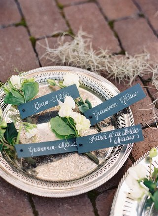silver-tray-platter-with-boutonniere-white-flower-green-leaves-tags-with-calligraphy-naming-recipien