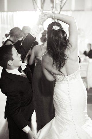 brides-son-spins-mom-around-black-tuxedo-trumpet-wedding-gown-having-fun