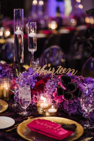 laser-cut-table-number-sticking-out-of-purple-flowers-modern-calligraphy-purple-centerpiece-ideas