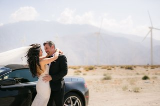 bride-in-galia-lahav-wedding-dress-and-groom-in-tuxedo-by-wind-mills-and-aston-martin-car-desert