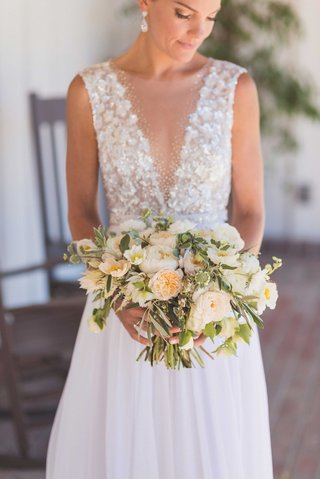 bride-in-mira-zwillinger-wedding-dress-from-carines-bridal-atelier-holding-rustic-wedding-bouquet