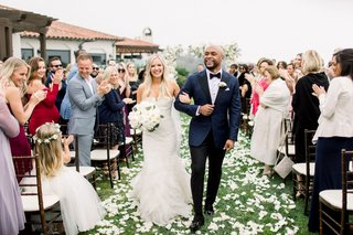 bride-and-groom-shane-vereen-taylour-rutledge-grass-lawn-flower-petals-guests-in-wood-chairs-claps