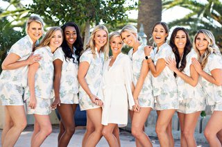 bride-in-white-robe-with-bridesmaids-in-short-pajamas-with-blue-green-hydrangea-flower-print-design