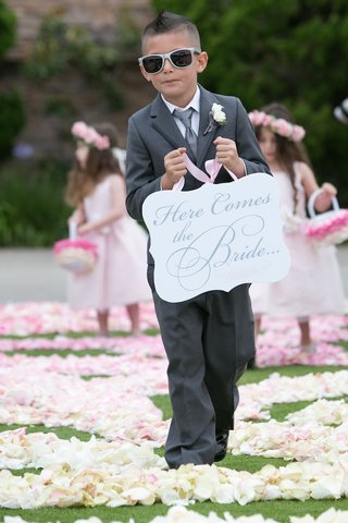 ring-bearer-in-grey-suit-holding-die-cut-here-comes-the-bride-sign
