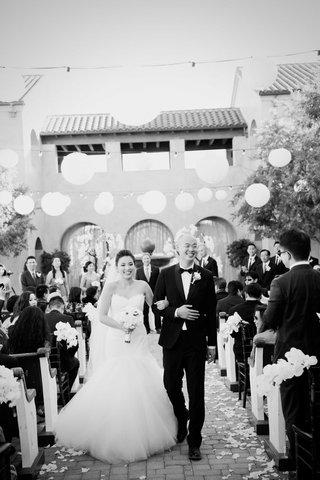 black-and-white-photo-of-bride-in-romona-keveza-dress-groom-in-tux-paper-lantern-decor