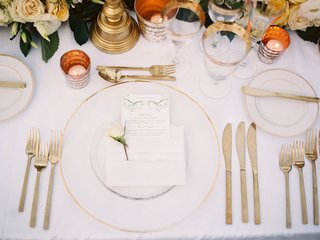 place-setting-white-linens-and-plates-gold-detailing-gold-utensils-glasses-candles-low-florals