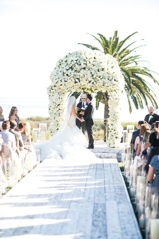 white-wash-wood-aisle-plank-runner-candles-along-side-white-flower-arch-chuppah-design-palm-trees